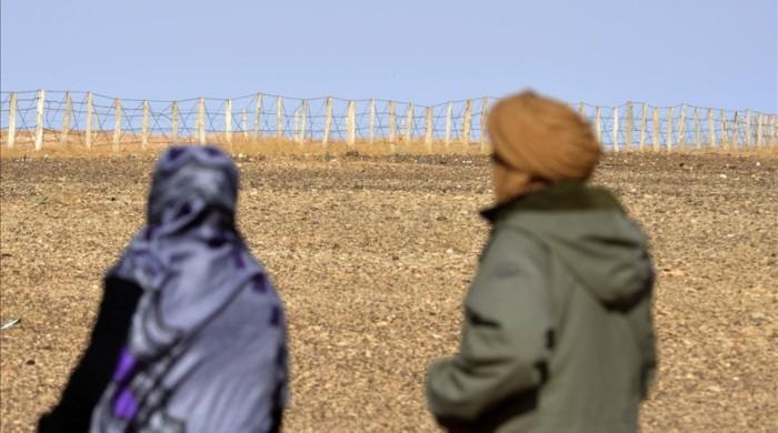 zghala-una-mujer-del-sahara-occidental-mira-hacia-valla-area-al-mahbes-mientras-acompana-hijo-anos-para-mostrarle-muro-que-separa-marruecos-zona-controlada-por-polisario-febrero-del-2017-1487367518313.jpg